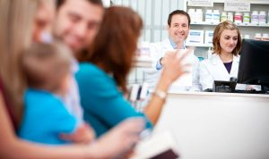 Pharmacist waving at a patient from behind the counter.