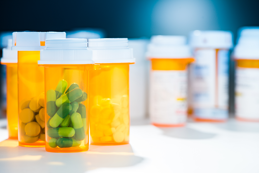 Pill bottles with various coloured pills inside