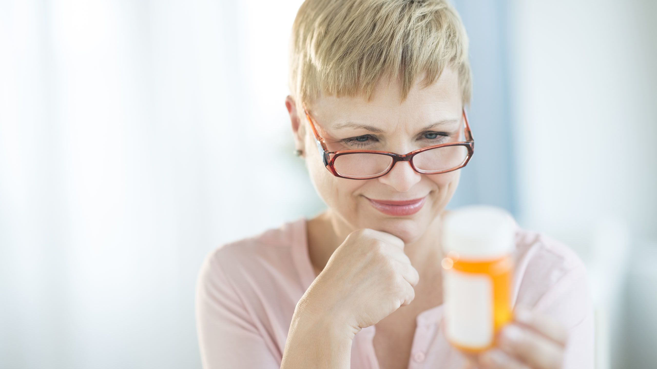 Woman with glasses reading the instructions on her pill bottle