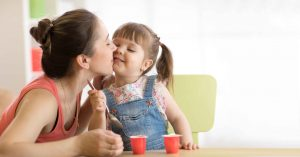 Mother kissing her daughter on the cheek while they eat yogurt